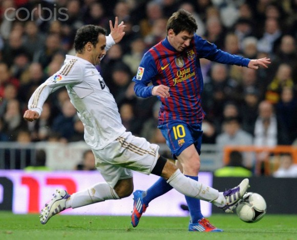 Barcelona's Messi is challenged by Real Madrid's Carvalho during their Spanish King's Cup soccer match in Madrid