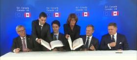Jean-Claude Juncker (à esquerda) olha para Justin Trudeau enquanto este partilha uma piada com Donald Tusk (à direita) durante a cerimónia de assinatura do CETA.